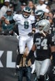 Nov 3, 2013; Oakland, CA, USA; Philadelphia Eagles quarterback Nick Foles (9) and receiver Riley Cooper (14) celebrate after combining on a 17-yard touchdown play in the second quarter as Oakland Raiders safety Charles Woodson (24) watches at O.co Coliseum. Mandatory Credit: Kirby Lee-USA TODAY Sports