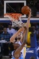 November 14, 2013; Oakland, CA, USA; Golden State Warriors center Andrew Bogut (12, top) shoots the ball against Oklahoma City Thunder center Hasheem Thabeet (34) during the first quarter at Oracle Arena. Mandatory Credit: Kyle Terada-USA TODAY Sports