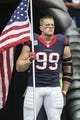 Nov 17, 2013; Houston, TX, USA; Houston Texans defensive end J.J. Watt (99) carries a flag onto the field before a game against the Oakland Raiders at Reliant Stadium. The Raiders defeated the Texans 28-23. Mandatory Credit: Troy Taormina-USA TODAY Sports