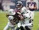 Nov 17, 2013; Houston, TX, USA; Houston Texans receiver Keshawn Martin (82) is tackled by Oakland Raiders cornerback Mike Jenkins (21) and safety Charles Woodson (24) at Reliant Stadium. The Raiders defeated the Texans 28-23. Mandatory Credit: Kirby Lee-USA TODAY Sports