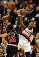Nov 22, 2013; Portland, OR, USA; Portland Trail Blazers point guard Damian Lillard (0) passes the ball as he is pressured by Chicago Bulls shooting guard Kirk Hinrich (12) and power forward Taj Gibson (22)  during the fourth quarter of the game at the Moda Center. The Blazers won the game 98-95. Mandatory Credit: Steve Dykes-USA TODAY Sports