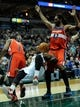 Nov 27, 2013; Milwaukee, WI, USA; Milwaukee Bucks guard O.J. Mayo (00) takes a fall after grabbing a rebound between Washington Wizards guard John Wall (2) and forward Nene Hilario (42) in the 3rd quarter at BMO Harris Bradley Center. Mandatory Credit: Benny Sieu-USA TODAY Sports