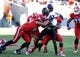 Nov 30, 2013; Raleigh, NC, USA; Maryland Terrapins receiver Levern Jacobs (8) is tackled by North Carolina State Wolfpack defenders D.J. Green (obscured) and Robert Caldwell (48) during the first half at Carter Finley Stadium. Mandatory Credit: Rob Kinnan-USA TODAY Sports
