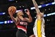 December 1, 2013; Los Angeles, CA, USA; Portland Trail Blazers point guard Damian Lillard (0) goes in for a basket against the defense of Los Angeles Lakers center Robert Sacre (50) during the first half at Staples Center. Mandatory Credit: Gary A. Vasquez-USA TODAY Sports
