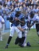 Nov 30, 2013; Chapel Hill, NC, USA; North Carolina Tar Heels quarterback Marquise Williams (12) runs as Duke Blue Devils safety Corbin McCarthy (26) and cornerback Deondre Singleton (33) defend in the fourth quarter. The Blue Devils defeated the Tar Heels 27-25 at Kenan Memorial Stadium. Mandatory Credit: Bob Donnan-USA TODAY Sports