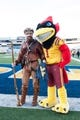 Nov 30, 2013; Morgantown, WV, USA; West Virginia Mountaineers  mascot Jonathan Kimble and Iowa State Cyclones mascot pose for photos prior to the game at Milan Puskar Stadium. The Iowa State Cyclones defeated West Virginia Mountaineers 52-44 in the third overtime. Mandatory Credit: Tommy Gilligan-USA TODAY Sports