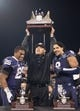 Dec 27, 2013; San Francisco, CA, USA; Washington Huskies head coach Marques Tuiasosopo holds up the Kraft Fight Hunger Bowl championship trophy with running back Bishop Sankey (25) and defensive end Hau'oli Kikaha (8) after defeating the Brigham Young Cougars 31-16 at AT&T Park. Mandatory Credit: Ed Szczepanski-USA TODAY Sports