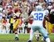 Dec 22, 2013; Landover, MD, USA; Washington Redskins quarterback Kirk Cousins (12) drops back to pass as Dallas Cowboys cornerback Orlando Scandrick (32) defends during the first half at FedEx Field. Mandatory Credit: Brad Mills-USA TODAY Sports