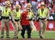 Dec 29, 2013; Phoenix, AZ, USA; An Arizona Cardinals fan is escorted off the field by police after running onto the field in the second half against the San Francisco 49ers at University of Phoenix Stadium. The 49ers defeated the Cardinals 23-20. Mandatory Credit: Mark J. Rebilas-USA TODAY Sports
