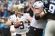 Dec 22, 2013; Charlotte, NC, USA; New Orleans Saints quarterback Drew Brees (9) looks to pass as Carolina Panthers defensive tackle Dwan Edwards (92) pressures in the second quarter at Bank of America Stadium. Mandatory Credit: Bob Donnan-USA TODAY Sports