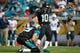 Dec 22, 2013; Jacksonville, FL, USA; Jacksonville Jaguars kicker Josh Scobee (10) kicks an extra point as Jacksonville Jaguars punter Bryan Anger (19) holds the ball during the first half against the Tennessee Titans at EverBank Field. Mandatory Credit: Kim Klement-USA TODAY Sports