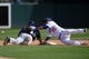 Mar 2, 2014; Phoenix, AZ, USA; An attempt to pick off San Diego Padres shortstop Jace Peterson (74) tags base in front of Los Angeles Dodgers shortstop Miguel Rojas (72) at Camelback Ranch. Mandatory Credit: Joe Camporeale-USA TODAY Sports