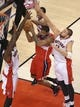 Feb 27, 2014; Toronto, Ontario, CAN; Washington Wizards forward Trevor Ariza (1) is guarded as he goes to the basket against Toronto Raptors forward Amir Johnson (15) and guard DeMar DeRozan (10) and center Jonas Valanciunas (17) at Air Canada Centre. The Wizards beat the Raptors 134-129 in triple overtime. Mandatory Credit: Tom Szczerbowski-USA TODAY Sports