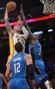 Mar 23, 2014; Los Angeles, CA, USA; Los Angeles Lakers center Robert Sacre (50) shoots the ball as Orlando Magic players Tobias Henry (12) and Dewayne Dedmon (12) defend at Staples Center. The Lakers won 103-94. Mandatory Credit: Kirby Lee-USA TODAY Sports