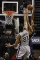 Mar 29, 2014; San Antonio, TX, USA; New Orleans Pelicans center Alexis Ajinca (42) goes for a dunk as he is defended by San Antonio Spurs forward Tim Duncan (21) during the second half at AT&T Center. The Spurs won 96-80. Mandatory Credit: Soobum Im-USA TODAY Sports