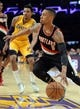 Apr 1, 2014; Los Angeles, CA, USA; Portland Trail Blazers guard Damian Lillard (0) drives to the basket past Los Angeles Lakers guard Kent Bazemore (6) during the first half of the game at Staples Center. Mandatory Credit: Jayne Kamin-Oncea-USA TODAY Sports