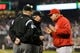 Apr 8, 2014; Seattle, WA, USA; Los Angeles Angels manager Mike Scioscia (14) talks with first base umpire Mike Winters (33) (center) after a review and overturn of a dropped ball by Los Angeles Angels left fielder Josh Hamilton (32) (not pictured) during the fifth inning against the Seattle Mariners at Safeco Field. Mandatory Credit: Steven Bisig-USA TODAY Sports