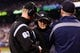 Apr 8, 2014; Seattle, WA, USA; Third base umpire Seth Buckminster (67) (left) and first base umpire Mike Winters (33) (center) review and overturn a dropped ball by Los Angeles Angels left fielder Josh Hamilton (32) (not pictured) during the fifth inning against the Seattle Mariners at Safeco Field. Mandatory Credit: Steven Bisig-USA TODAY Sports