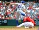April 13, 2014; Anaheim, CA, USA; New York Mets second baseman Daniel Murphy (28) throws to first to complete an out as  Los Angeles Angels center fielder Mike Trout (27) slides into second in the fourth inning at Angel Stadium of Anaheim. Mandatory Credit: Gary A. Vasquez-USA TODAY Sports