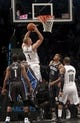 Apr 13, 2014; Brooklyn, NY, USA; Brooklyn Nets forward Mason Plumlee (1) puts up a shot against Orlando Magic guard Doron Lamb (1) and Orlando Magic forward Tobias Harris (12) in the first quarter at Barclays Center. Mandatory Credit: Nicole Sweet-USA TODAY Sports