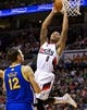 Apr 13, 2014; Portland, OR, USA; Portland Trail Blazers guard Damian Lillard (0) shoots over Golden State Warriors center Andrew Bogut (12) during the fourth quarter at the Moda Center. Mandatory Credit: Craig Mitchelldyer-USA TODAY Sports