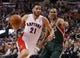 Apr 14, 2014; Toronto, Ontario, CAN; Toronto Raptors guard Greivis Vasquez (21) carries the ball past Milwaukee Bucks guard Ramon Sessions (13) at the Air Canada Centre. Toronto defeated Milwaukee 110-100. Mandatory Credit: John E. Sokolowski-USA TODAY Sports