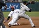 Apr 18, 2014; Arlington, TX, USA; Texas Rangers shortstop Elvis Andrus (1) slides to third base ahead of the throw to Chicago White Sox third baseman Marcus Semien (5) on a hit by Alex Rios during the first inning at Rangers Ballpark in Arlington. Mandatory Credit: Jim Cowsert-USA TODAY Sports