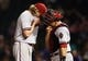 Apr 21, 2014; Chicago, IL, USA; Arizona Diamondbacks starting pitcher Bronson Arroyo (left) and catcher Miguel Montero (right) cover their mouths as they talk on the mound during the sixth inning against the Chicago Cubs at Wrigley Field. Mandatory Credit: Jerry Lai-USA TODAY Sports