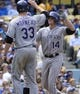 Apr 27, 2014; Los Angeles, CA, USA; Colorado Rockies second baseman Josh Rutledge (14) is congratulated by teammate first baseman Justin Morneau (33) after hitting a 3-run homer in the sixth inning against the Los Angeles Dodgers at Dodger Stadium. Mandatory Credit: Robert Hanashiro-USA TODAY Sports