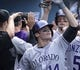 Apr 27, 2014; Los Angeles, CA, USA; Colorado Rockies second baseman Josh Rutledge (14) is congratulated in the Rockies dugout after slugging a 3-run homer in the 6th inning against the Los Angeles Dodgers at Dodger Stadium. Mandatory Credit: Robert Hanashiro-USA TODAY Sports