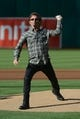 May 10, 2014; Oakland, CA, USA; Musical group Journey keyboardist Jonathan Cain throws out the ceremonial first pitch before the game between the Oakland Athletics and the Washington Nationals at O.co Coliseum. The Athletics defeated the Nationals 4-3 in 10 innings. Mandatory Credit: Kyle Terada-USA TODAY Sports
