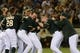 May 10, 2014; Oakland, CA, USA; Oakland Athletics players celebrate after catcher John Jaso (5, third from right) hit the game-winning RBI-double in the 10th inning against the Washington Nationals at O.co Coliseum. The Athletics defeated the Nationals 4-3 in 10 innings. Mandatory Credit: Kyle Terada-USA TODAY Sports