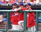 May 18, 2014; Philadelphia, PA, USA; (left to right) Philadelphia Phillies starting pitcher Cole Hamels (35) and starting pitcher A.J. Burnett (34) and starting pitcher Kyle Kendrick (38) watch from the dugout in a game against the Cincinnati Reds at Citizens Bank Park. The Phillies won 8-3. Mandatory Credit: Bill Streicher-USA TODAY Sports