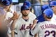 Jun 12, 2014; New York, NY, USA; New York Mets starting pitcher Jonathon Niese (49) high-fives teammates in the dugout after being taken out against the New York Mets during the eighth inning at Citi Field. The Brewers won 5-1 in thirteen innings. Mandatory Credit: Brad Penner-USA TODAY Sports