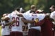 Jun 17, 2014; Ashburn, VA, USA; Washington Redskins running back Alfred Morris (46) huddles with teammates and running backs coach Randy Jordan (right) after a minicamp session at Redskins Park. Mandatory Credit: Geoff Burke-USA TODAY Sports