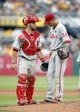 Jul 6, 2014; Pittsburgh, PA, USA; Philadelphia Phillies catcher Cameron Rupp (left) talks with starting pitcher A.J. Burnett (34) against the Pittsburgh Pirates during the seventh inning at PNC Park. The Pirates won 6-2. Mandatory Credit: Charles LeClaire-USA TODAY Sports