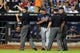 Jul 7, 2014; New York, NY, USA; Atlanta Braves manager Fredi Gonzalez (33) is thrown out of a game by umpire Mike Everitt (57) after arguing a reviewed call with umpires Everitt and Tim Timmons (95) and Sean Barber (29) during the ninth inning of a game against the New York Mets at Citi Field. Mandatory Credit: Brad Penner-USA TODAY Sports