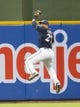 Jul 8, 2014; Milwaukee, WI, USA; Milwaukee Brewers center fielder Carlos Gomez (27) makes a leaping catch during the second inning against the Philadelphia Phillies at Miller Park. Mandatory Credit: Jeff Hanisch-USA TODAY Sports