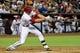 Jul 8, 2014; Phoenix, AZ, USA; Arizona Diamondbacks shortstop Nick Ahmed (13) hits a single during the second inning against the Miami Marlins at Chase Field. Mandatory Credit: Matt Kartozian-USA TODAY Sports