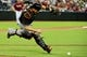Jul 9, 2014; Phoenix, AZ, USA; Miami Marlins catcher Jeff Mathis (6) fields a ball hit by Arizona Diamondbacks third baseman Martin Prado (not pictured) during the fourth inning at Chase Field. Mandatory Credit: Matt Kartozian-USA TODAY Sports