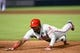 Jul 19, 2014; Atlanta, GA, USA; Philadelphia Phillies left fielder Domonic Brown (9) dives back to first base against the Atlanta Braves during the eighth inning at Turner Field. The Phillies defeated the Braves 2-1. Mandatory Credit: Dale Zanine-USA TODAY Sports