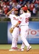 Jul 25, 2014; Philadelphia, PA, USA; Philadelphia Phillies shortstop Jimmy Rollins (11) and second baseman Chase Utley (26) high five each other at the conclusion of a game against the Arizona Diamondbacks at Citizens Bank Park. The Phillies won 9-5. Mandatory Credit: Bill Streicher-USA TODAY Sports