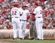 Aug 8, 2014; Cincinnati, OH, USA; Cincinnati Reds manager Bryan Price (38), first base coach Billy Hatcher (22) and trainer talk to catcher Brayan Pena (29) after an apparent injury to his leg during the second inning against the Miami Marlins at Great American Ball Park. Mandatory Credit: Frank Victores-USA TODAY Sports
