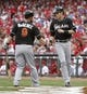 Aug 9, 2014; Cincinnati, OH, USA; Miami Marlins left fielder Christian Yelich (21) is congratulated by third baseman Casey McGehee (9) after Yelich scored on a sacrifice fly by Giancarlo Stanton (not pictured) in the first inning against the Cincinnati Reds at Great American Ball Park. Mandatory Credit: David Kohl-USA TODAY Sports